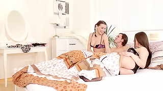 Two babes are in a threesome, smiling and receiving a cock