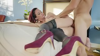 A redhead with a nice pair of tits is giving a blow job on the bed