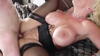 Busty blonde in dark garter and stockings gives guy a titjob before he rams her cunt on the bed.