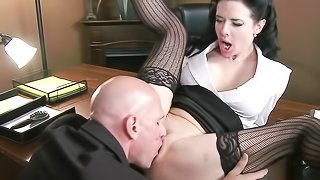 Submissive brunette secretary in see-though lingerie gets ball-gag in her mouth and rammed on the desk.