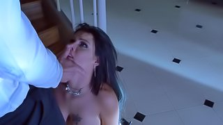 A black haired woman that has huge tits is kissing a big dick
