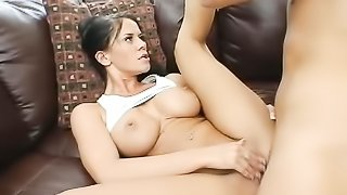 Delightful brunette tennis player in white sports bra and miniskirt blows guy's hard cock before riding him on brown couch.