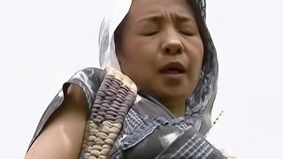 Mature Asian woman with big tits enjoying a hardcore fuck in a field