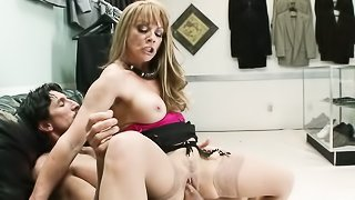 Blonde cougar wearing black garter and light stockings blows tailor's cock and rides him on black leather couch.
