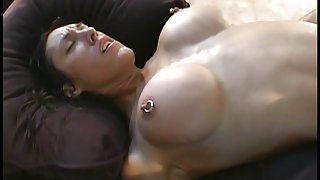 Brunette with pierced plastic tits sucks cock then climbs aboard dude's dick