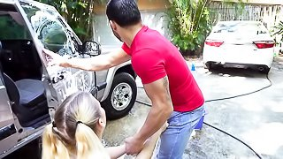 Skinny young blonde with pigtailed hair and long black nails kneels on the cement by the car she's washing and lifts her thin white top and sucks cock outdoors