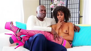 Flirtatious ebony vixen in stockings enjoys a topless interview on the couch