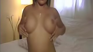 Young woman in white lingerie uses a dildo to masturbate.