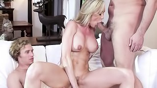 Horny blonde housewife in green dress gets fucked by tow construction workers on the white living room couch.