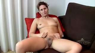 Inge talks on the couch and reveals hairy pussy
