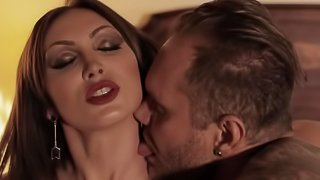 A brunette with a sexy body is giving a blow job on the bed