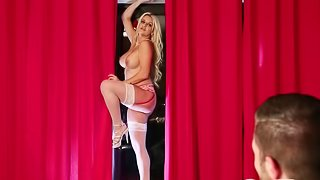 A blonde is near a red curtain, displaying her own meat curtains
