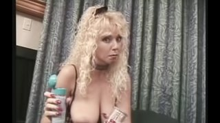Wavy haired cougar in fishnets fits huge toy in her pussy close up