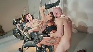 Inked biker sluts in leather boots share a big cock