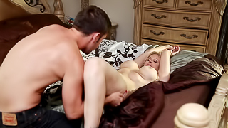 A sexy mature blonde is getting her tits pushed together and fucked