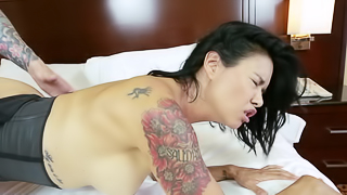 A raven haired girl with tattoos is on the bed, having a grand time