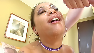 A black woman is getting cum all over her sexy face in this scene