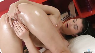 Watch oiled brunette fingering pussy