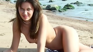 Long haired solo model fingering her pink slit on the beach