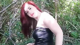 Redhead in a black get-up pissing in the middle of nowhere