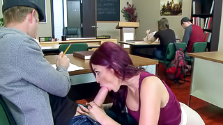 A redhead that is wearing glasses is doing a blow job in the classroom