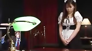Lusty maid bends over on a wooden desk and shows her white panty under her black and white dress then lets her master grab her hot ass.