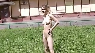 Busty amateur chick is walking naked on the grass